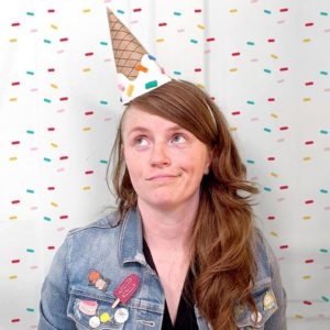 Person in ice cream party hat with popsicle pin