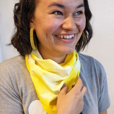 Jill smiles wearing a yellow tie dyed bandana and a friendship bracelet